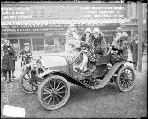 Women sitting in a car in front of the Belmont Theater, 1927
